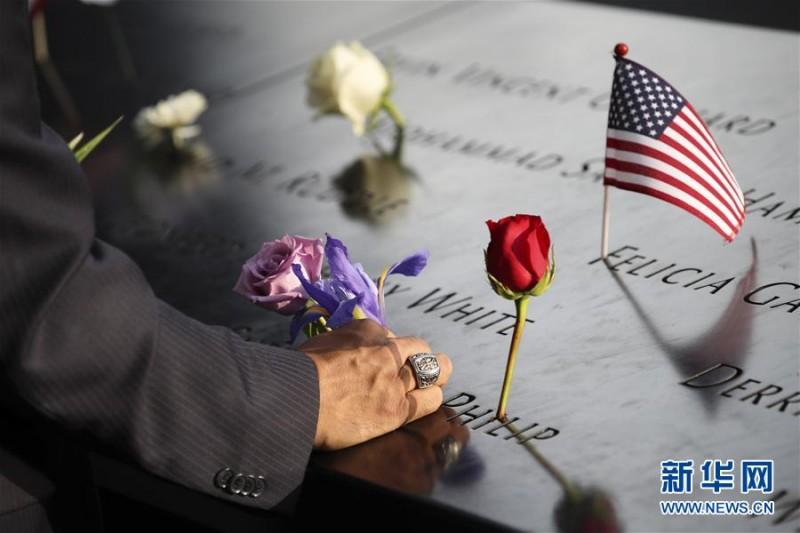 """9月11日,在美国纽约的""""9·11""""遗址纪念广场,一名男子将鲜花插在刻有遇难者姓名的铜牌上。    当天是""""9·11""""事件16周年纪念日,人们来到纽约""""9·11""""遗址纪念广场,向死难者致以哀悼,对牺牲的救援人员表达敬意。9月11日,在美国纽约的""""9·11""""遗址纪念广场,  一名男子将鲜花插在刻有遇难者姓名的铜牌上。新华社记者 王迎摄"""