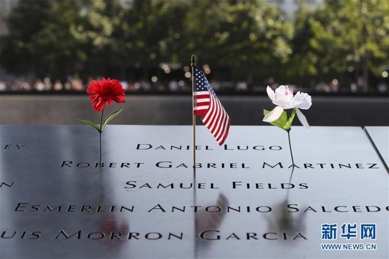 """9月11日,在美国纽约的""""9·11""""遗址纪念广场,刻有遇难者姓名的铜牌上摆放着鲜花和美国国旗。   当天是""""9·11""""事件16周年纪念日,人们来到纽约""""9·11""""遗址纪念广场,向死难者致以哀悼,对牺牲的救援人员表达敬意。9月11日,在美国纽约的""""9·11""""遗址纪念广场,  一名男子将鲜花插在刻有遇难者姓名的铜牌上。新华社记者 王迎摄"""