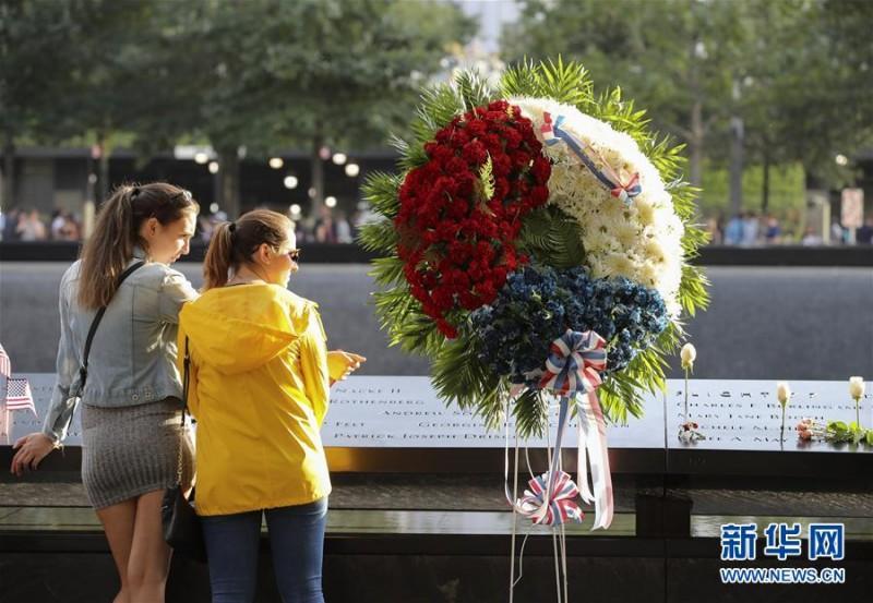 """9月11日,在美国纽约的""""9·11""""遗址纪念广场,人们在镶嵌遇难者姓名铜牌的纪念池旁悼念逝者。   当天是""""9·11""""事件16周年纪念日,人们来到纽约""""9·11""""遗址纪念广场,向死难者致以哀悼,对牺牲的救援人员表达敬意。9月11日,在美国纽约的""""9·11""""遗址纪念广场,  一名男子将鲜花插在刻有遇难者姓名的铜牌上。新华社记者 王迎摄"""