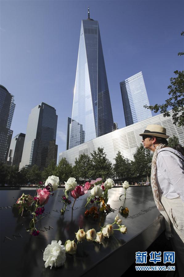 """9月11日,在美国纽约的""""9·11""""遗址纪念广场,刻有遇难者姓名的铜牌上摆放着鲜花。    当天是""""9·11""""事件16周年纪念日,人们来到纽约""""9·11""""遗址纪念广场,向死难者致以哀悼,对牺牲的救援人员表达敬意。9月11日,在美国纽约的""""9·11""""遗址纪念广场,一名男子将鲜花插在刻有遇难者姓名的铜牌上。新华社记者 王迎摄"""