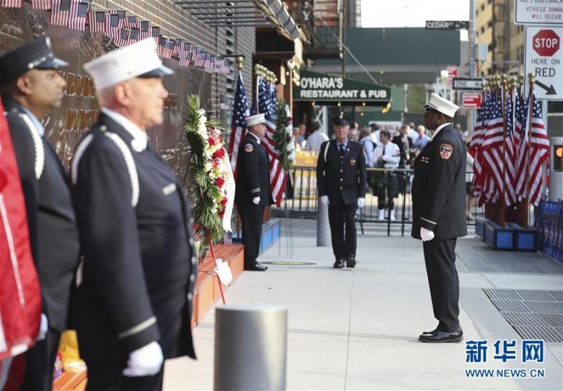 """9月11日,在美国纽约""""9·11""""遗址纪念广场旁的消防员纪念墙前,纽约消防员设立纪念岗纪念逝者。    当天是""""9·11""""事件16周年纪念日,人们来到纽约""""9·11""""遗址纪念广场,向死难者致以哀悼,对牺牲的救援人员表达敬意。9月11日,在美国纽约的""""9·11""""遗址纪念广场,  一名男子将鲜花插在刻有遇难者姓名的铜牌上。新华社记者 王迎摄"""