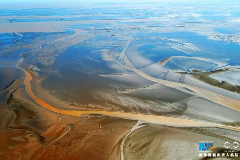 江苏盐城湿地珍禽国家级自然保护区有着芦苇丛生的天然植被、丰富多样的滩涂生物,是禽类生活的理想场所。这里是中国第一个滩涂型自然保护区。每年成群的丹顶鹤结队飞到这里越冬,为世界上最大的野生丹顶鹤群集结地之一。图为色彩斑斓的湿地滩涂,广袤无垠。新华网 陈国远摄