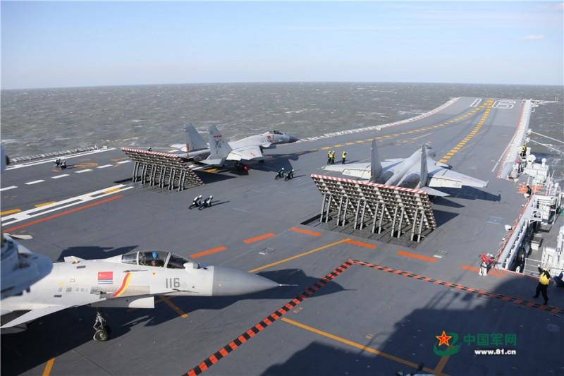 歼-15舰载战斗机依次从辽宁舰起飞参加实弹射击演习。 莫小亮摄影