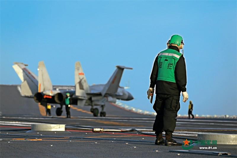 歼-15舰载战斗机成功着舰后,阻拦索检查员查看阻拦索复位情况。