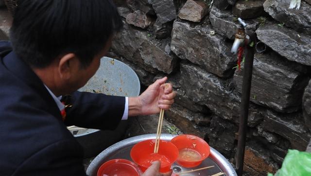 在距离大锅饭的不远处,堆放着清一色的红碗和筷子,客人们自己动手拿碗筷去盛饭。