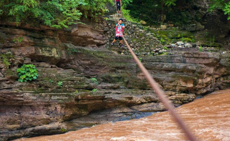 早前,一名妇女出外采购物资,从铁索上渡过西溪河返村。围绕着阿布洛哈的西溪河是金沙江的一条支流,从去年开始,金沙江溪洛渡水电站大坝开始蓄水,导致西溪河水位上涨,淹没了出行的通道。(摄影:毕利新)