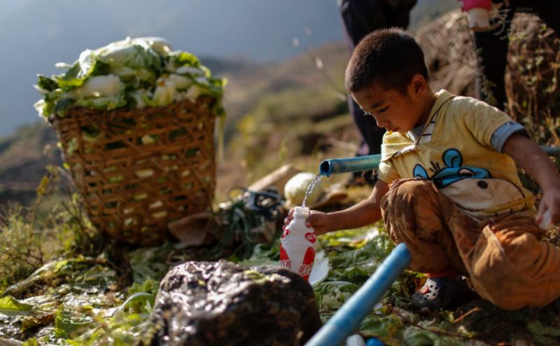 通往阿布洛哈村三组的路边,一个孩子正在水管接驳处接水。之前的引水工程,很多水管出现堵塞、破裂等情况,导致很多户家庭断水。村里的小学也经常断水,很多时候孩子们吃不上饭。