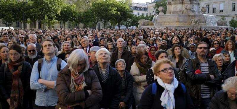 """4月17日,在法国巴黎,人们聚集在一起为巴黎圣母院祈福。 法国负责调查巴黎圣母院大火的检察官雷米·海茨17日说,目前火灾原因主要指向""""事故因素""""。初步调查显示,倒塌的塔尖下方可能是最初的起火点。巴黎圣母院15日突发火灾,圣母院的屋顶和塔尖被烧毁,但主体建筑得以保存。"""