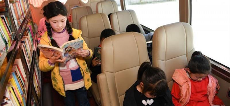 """4月17日,岳西县冶溪镇白沙小学学生在""""汽车图书馆""""上阅读。当日,安徽向日葵公益助学服务中心联合合肥市少年儿童图书馆开展""""流动的书香——一本图书的爱心之旅""""活动,为安徽省岳西县冶溪镇白沙小学的学生们捐赠600多册图书,并设立""""汽车图书馆"""",为山区学生提供阅读便利。"""