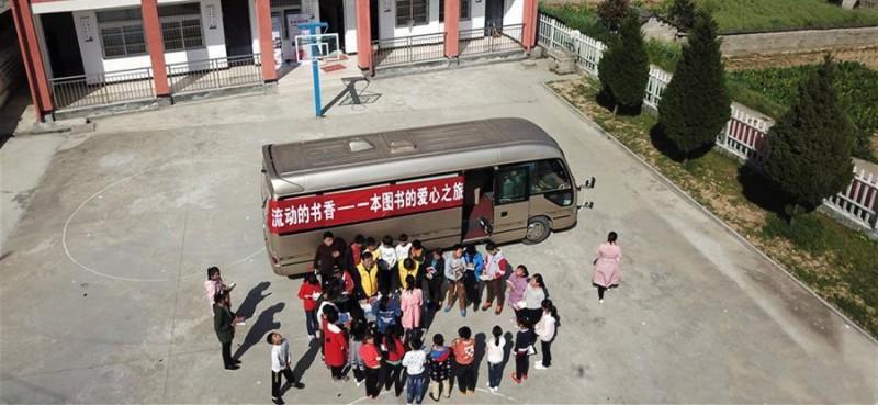 """4月17日,岳西县冶溪镇白沙小学学生在领取爱心图书(无人机拍摄)。当日,安徽向日葵公益助学服务中心联合合肥市少年儿童图书馆开展""""流动的书香——一本图书的爱心之旅""""活动,为安徽省岳西县冶溪镇白沙小学的学生们捐赠600多册图书,并设立""""汽车图书馆"""",为山区学生提供阅读便利。"""