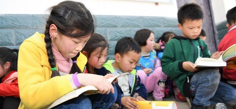 """4月17日,岳西县冶溪镇白沙小学学生领取爱心图书后阅读。当日,安徽向日葵公益助学服务中心联合合肥市少年儿童图书馆开展""""流动的书香——一本图书的爱心之旅""""活动,为安徽省岳西县冶溪镇白沙小学的学生们捐赠600多册图书,并设立""""汽车图书馆"""",为山区学生提供阅读便利。"""