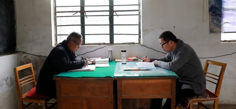 3月26日,董运青老师(左)和王峰老师(右)在简陋的办公室里备课、批改作业。