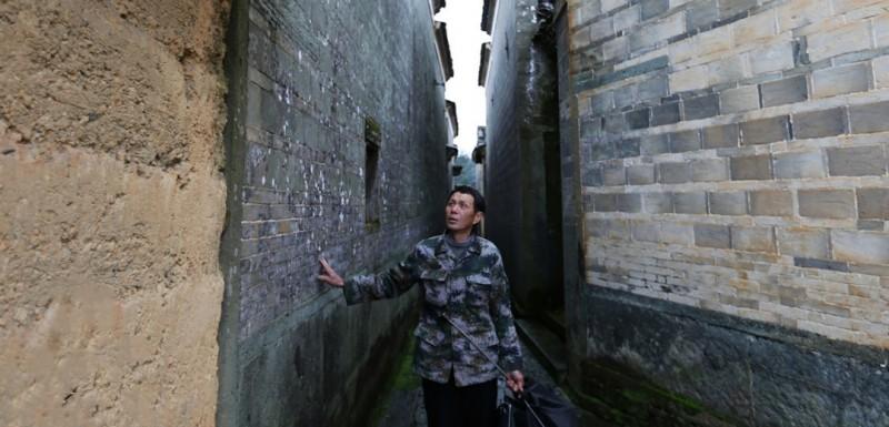 时下正值雨季,一大早,金溪县游垫古村的文保员胡庆华便提伞出门,准备前往村里的老宅查看是否出现漏雨破损情况。天晴怕木梁爆裂土墙倒塌、下雨查屋顶漏水墙壁透风……每天在村里来回巡查走上一圈,是今年66岁的胡庆华每天都要做的事情。图为胡庆华正在村内巡视。