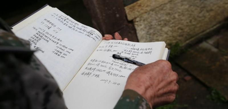 为保护老屋原有的历史价值不被破坏,胡庆华找来隔壁村的专业泥瓦匠和经验丰富的老匠人。加固柱子、换梁、换瓦、补墙……经过近一年的施工,原本摇摇欲坠的老屋被成功抢救。图为胡庆华正在记录老屋的维修情况。
