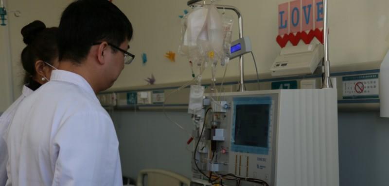 医生在观察血细胞分离机的工作情况。