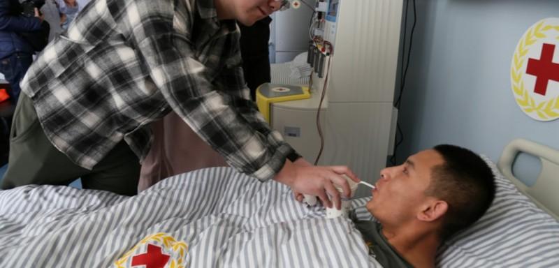 """同事在给卫立强喂水。完成这次造血干细胞的采集持续约4小时,采集完成后,造血干细胞将由配型成功患者所在医院的医生带走,去完成接下来的""""生命接力""""。"""