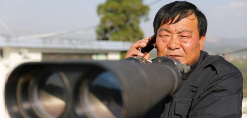 在每年长达半年的森林防火期内,夫妇俩每天24小时坚守在瞭望台,随时对可视范围进行瞭望观测,发现火情及时向当地林业部门报告。图为张家富通过高倍望远镜监测林区,并向上级部门通报监测情况。