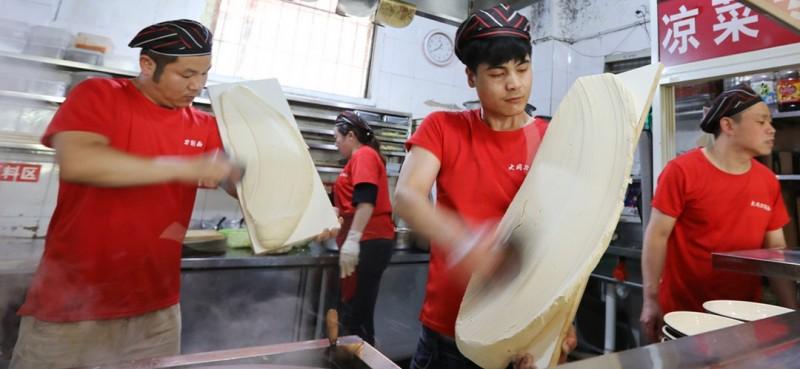 除了老板孙学青,店里的服务员、厨师共7名员工都是聋哑人,他们在这里奋斗并幸福着。图为2019年5月16日,开封市大王屯东街大同刀削面馆,厨师们在制作刀削面。
