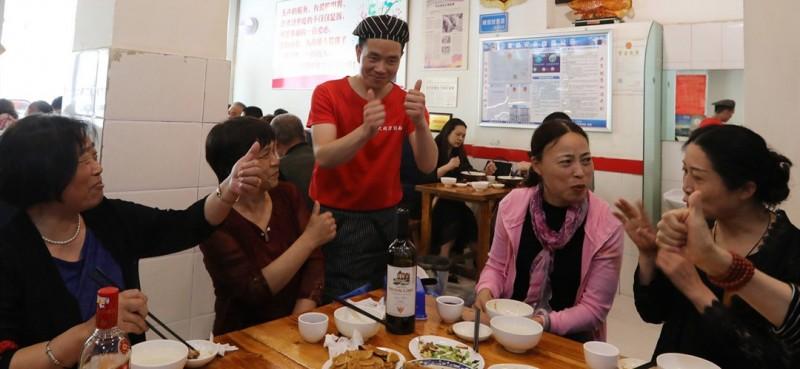大同刀削面馆的员工在用手语和顾客交流。