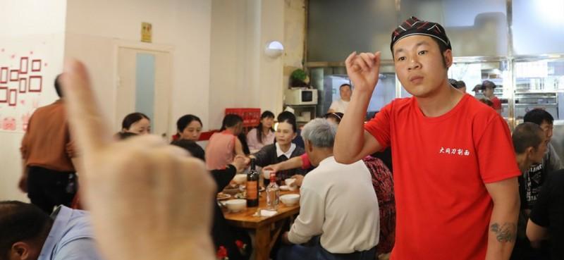 员工用手语传递点餐信息。