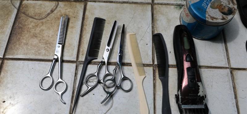 一把电推剪子、一把普通梳子、一块用废旧雨伞布制成的围布、一个电动车废旧后视镜、一个由红酒箱做成的工具箱,这就是邹勤敏用来剪发的装备。