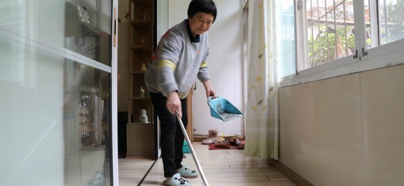 """除了帮老人剪头发,邹勤敏还会帮助他们做一些家务。""""有不少老人行动不太方便,我就在生活上能帮就帮一点。""""邹勤敏说。图为邹勤敏帮助老人打扫卫生。"""