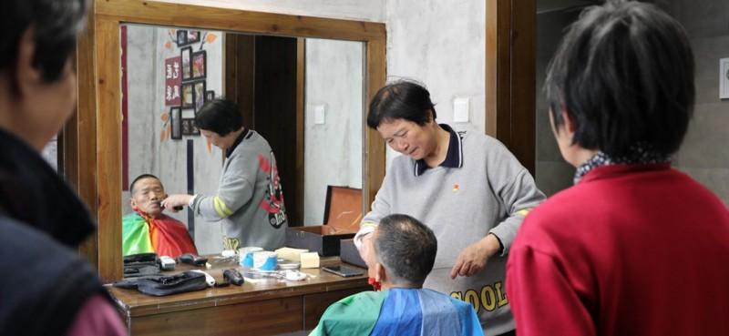 """""""社区安排了这个固定的理发点之后,我们找她剪头发更方便了,她不仅手艺好,还不要钱,是一位好党员,我觉得她就是传播正能量的使者,值得我们学习发扬。""""社区居民陈发莲说。邹勤敏正在为居民理发,还有人在排队等候。"""