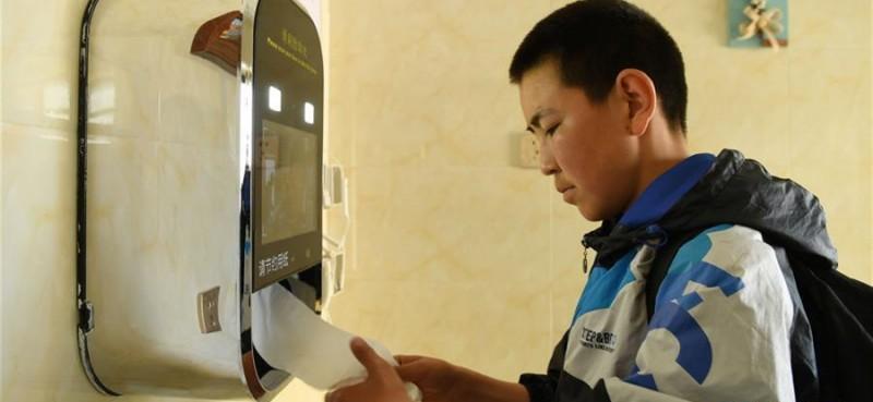一名学生在阿勒泰市区一公共厕所内通过人脸识别取纸。