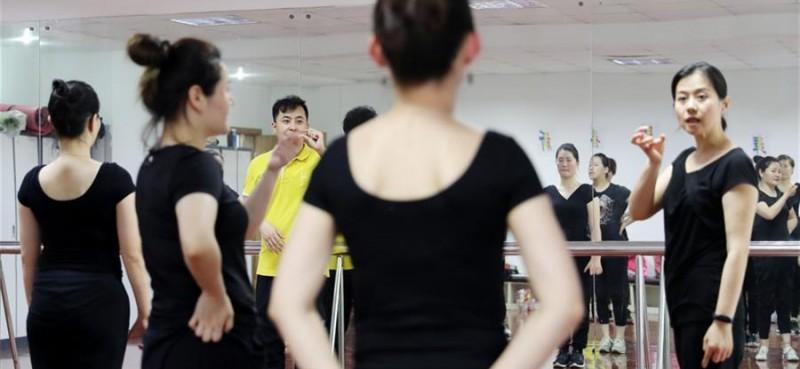 5月26日,两名舞蹈队员在聊天。 在上海闵行区古美路街道,有一个由听力障碍者组成的舞蹈团队——古美彩韵聋人舞蹈艺术队。舞蹈队现有20名队员,年龄从20岁到40岁,由上海戏剧学院舞蹈学院的老师每周一次为队员们提供训练指导。对舞蹈艺术的热爱,让这些听力障碍者走到了一起,在无声世界里舞出精彩人生。