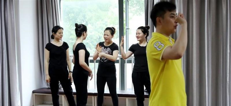 5月26日,舞蹈队员在训练间隙聊天。 在上海闵行区古美路街道,有一个由听力障碍者组成的舞蹈团队——古美彩韵聋人舞蹈艺术队。舞蹈队现有20名队员,年龄从20岁到40岁,由上海戏剧学院舞蹈学院的老师每周一次为队员们提供训练指导。对舞蹈艺术的热爱,让这些听力障碍者走到了一起,在无声世界里舞出精彩人生。