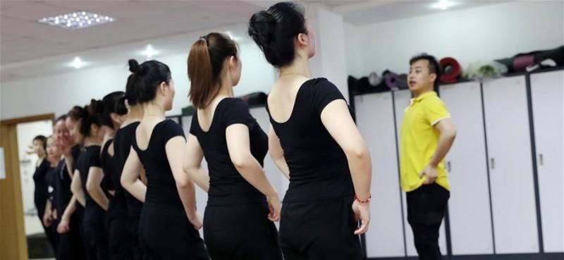 5月26日,舞蹈队员们在上海戏剧学院舞蹈学院刘建强老师(右)的带领下排练舞蹈。 在上海闵行区古美路街道,有一个由听力障碍者组成的舞蹈团队——古美彩韵聋人舞蹈艺术队。舞蹈队现有20名队员,年龄从20岁到40岁,由上海戏剧学院舞蹈学院的老师每周一次为队员们提供训练指导。对舞蹈艺术的热爱,让这些听力障碍者走到了一起,在无声世界里舞出精彩人生。