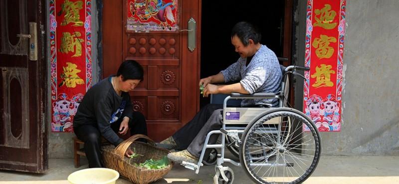 曾付学是湖北十堰市郧阳区大柳乡黄龙庙村村民,今年54岁。2006年他外出务工意外受伤导致高位截瘫,只能与轮椅为伴。图为曾付学和妻子陈满英在门前择菜。