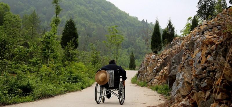 不甘心一辈子与轮椅为伴,曾付学决心用还能活动的双手做一点事情。2012年,他开始爬坡开荒造地。图为曾付学坐着轮椅去山坡造地。