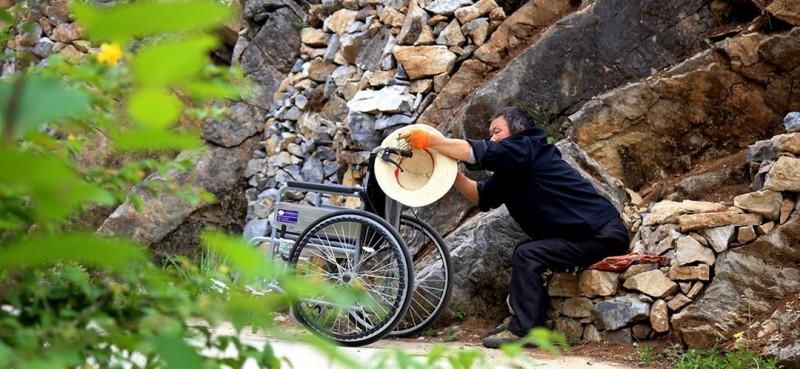 图为曾付学行至山跟前时,放下轮椅准备爬坡造地。