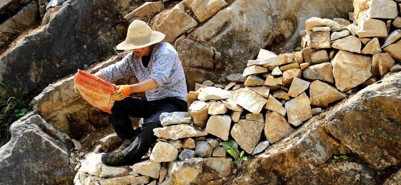 图为曾付学借助自制坐垫在他砌的石阶上向上挪移。