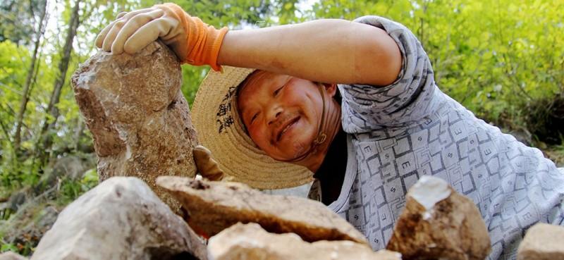 图为曾付学在造地砌石坎。