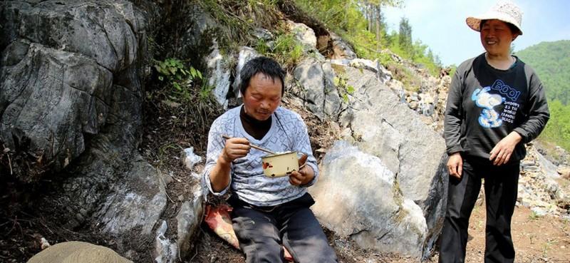 图为曾付学的妻子陈满英为他送午饭到山坡上,看着曾付学吃着自己做的可口饭菜,妻子露出笑容。
