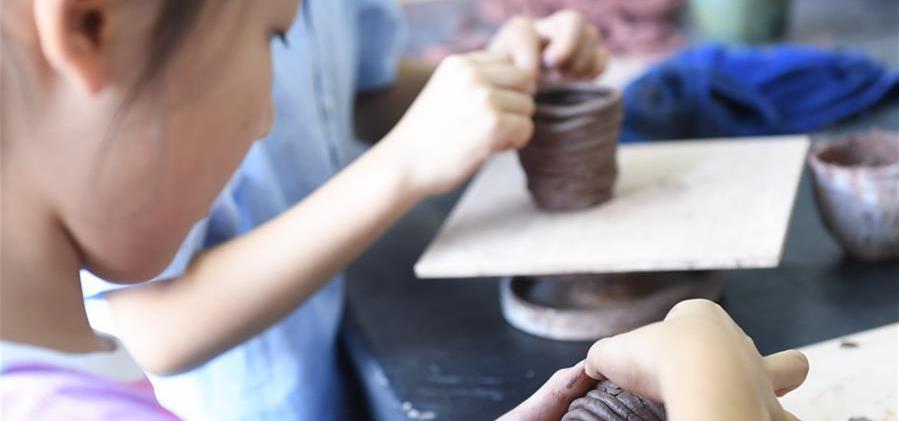 8月6日,孩子们在吴兴区青少年活动中心参加陶艺制作课。