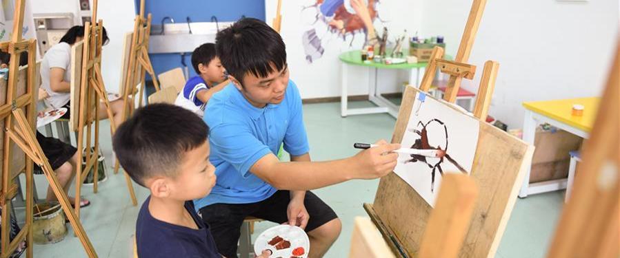 8月6日,志愿者在吴兴区青少年活动中心指导儿童进行绘画创作。