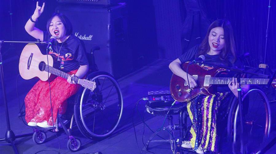 """8月14日,8772乐队成员崔莹(左)和程利婷在演唱会上表演。当日,由罕见病、残障人士组成的8772乐队在北京举办首张专辑《从不罕见》首唱会,近300名观众到场支持,并聆听了8772乐队的激情演唱。8772乐队是一支由罕见病、残障人士组成的乐队,乐队名字来自""""病痛挑战""""首字母拼音缩写""""BTTZ""""的变形。乐队首张专辑《从不罕见》收录了成立三年来的10首原创歌曲,作品出自患有成骨不全症、卡尔曼氏综合征、脊髓性肌萎缩症等罕见病的病友之手。他们希望通过这张专辑表达对音乐的热爱,并通过音乐为罕见病群体发声,并传达属于这个群体的生命态度。来源:新华网"""