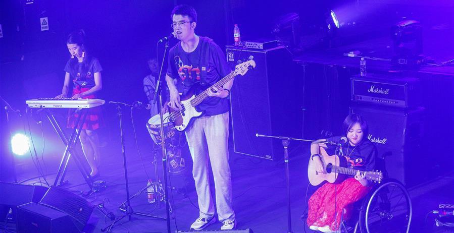 8月14日,8772乐队成员苏佳宇(中)在演唱会上表演。来源:新华网