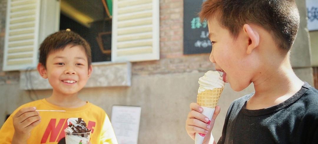 图为两位小朋品尝用捡烟头换到的冰淇淋。来源:新华网