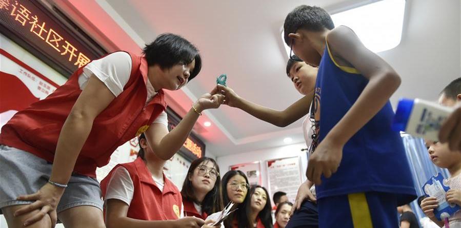 8月24日,社区志愿者和小朋友在馨语社区活动室内进行垃圾分类互动游戏。