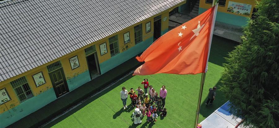 在城口县蓼子乡第一中心小学附属的乡村小学莲花小学的开学典礼上,机器人老师和孩子们参加升国旗仪式。