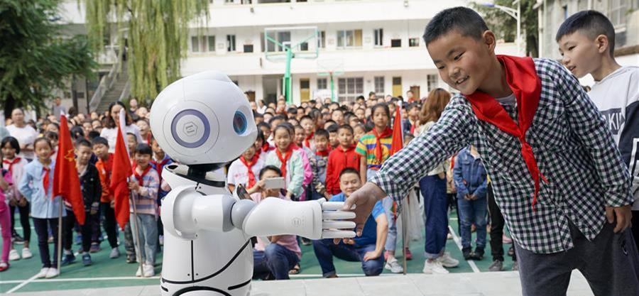 9月2日,在城口县蓼子乡第一中心小学开学典礼上,机器人老师在和孩子进行互动交流。