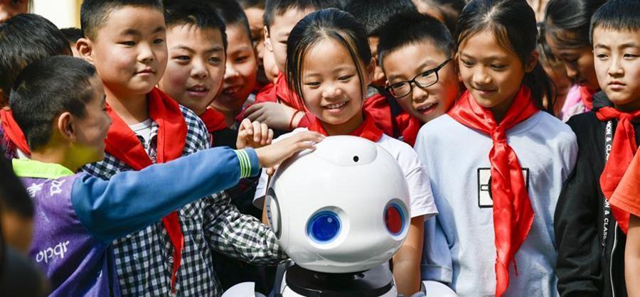 9月2日,在城口县蓼子乡第一中心小学开学典礼上,机器人老师和孩子们进行互动交流。