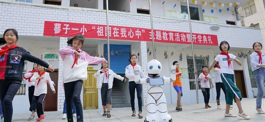 9月2日,在城口县蓼子乡第一中心小学开学典礼上,机器人老师和孩子们一起跳舞。