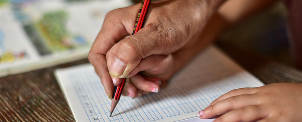 潘平忠老师手把手教学生写拼音字母。