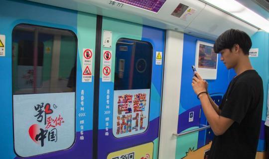 """近日,由武汉工商学院""""字绘中国""""团队参与设计的""""爱国车厢""""地铁专列正式发车,在武汉地铁2号线上运行。车厢内,""""青春湖北""""四个大字色彩活泼,十分吸睛。参与主题设计的武汉工商学院学生杨子豪介绍,这四个汉字采用了极具特色的字绘形式,将黄鹤楼、长江大桥、武当山、三峡大坝、赤壁古战场等湖北地标巧妙地融合在汉字中。据悉,该专列共设置了6节车厢,分别以""""理想、爱国、担当、奋斗、本领、品德""""为主题,尽显湖北青年的青春风采。图为地铁专列吸引年轻人前来拍照。"""