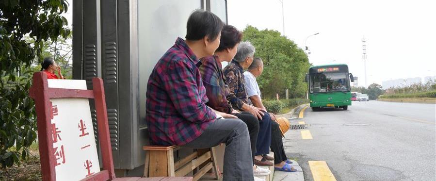 10月9日,在南昌市青山湖区顺外路口的公交车站,几名市民坐在爱心椅上候车。